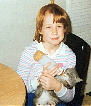 Melissa Moore as a child bottle-feeding a cat